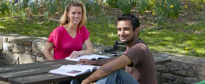A male and female student studying on a bench on campus