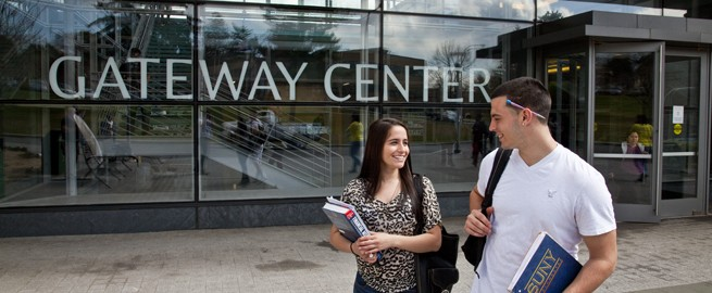 A Male and Female students conversing while walking in front of the Gateway Center building on the Valhalla campus