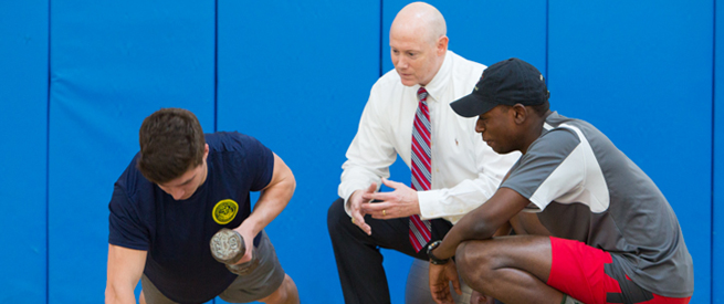 A personal training professor and student observe an athlete