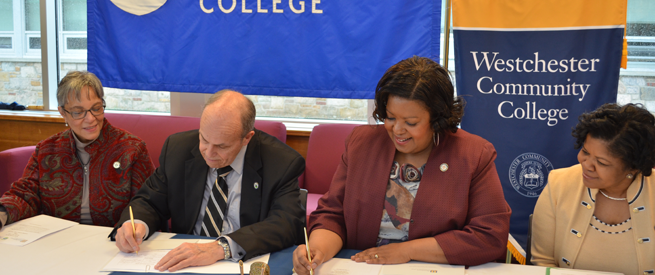 Representatives from Lehman College and Westchester Community College signing agreements