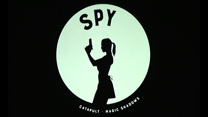 Spy promotional graphic with silhouette of character.